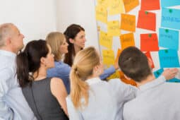 Group of People Talking Around Whiteboard